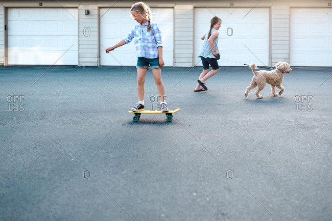 Girl riding on skateboard and girl running with dog