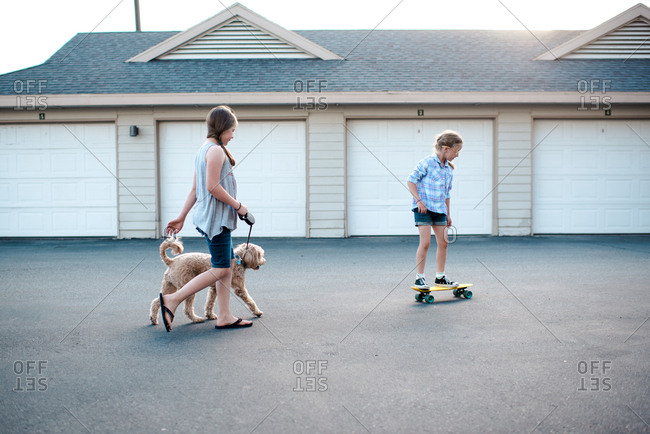 Girl walking her dog while her sister rides skateboard