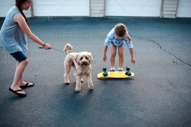 Girl holding leash on pet dog while her sister picks up skateboard
