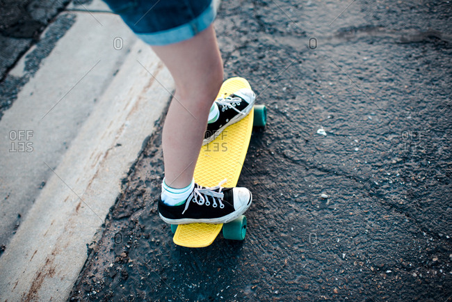 Legs of a girl riding a skateboard