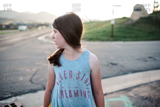 Girl with head turned looking down the road
