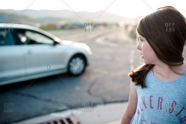 Girl watching a car make a turn on the street