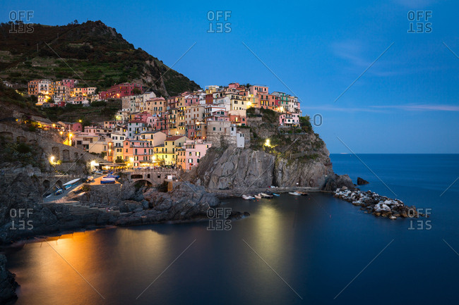 A long exposure at blue hour as the lights come on in the colorful town of Manarola, Cinque Terre, UNESCO World Heritage Site, Liguria, Italy, Europe