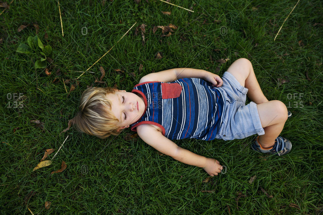 Overhead view of young toddler boy asleep on the grass