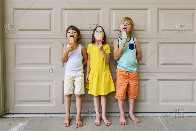 Three young kids eating popsicles in the summer