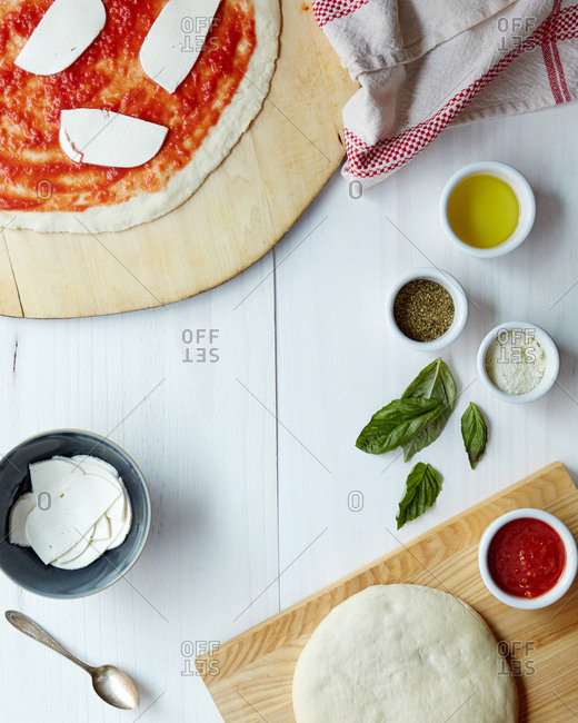 Margherita pizza being prepared with fresh ingredients from overhead