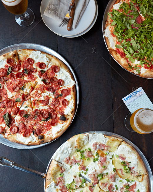 Three pizzas from overhead on a wood restaurant table
