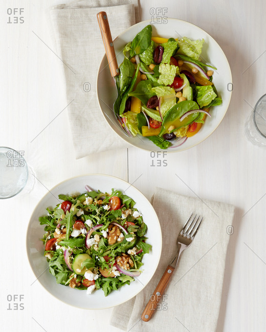 Two fresh salads overhead on a white washed wood surface from overhead