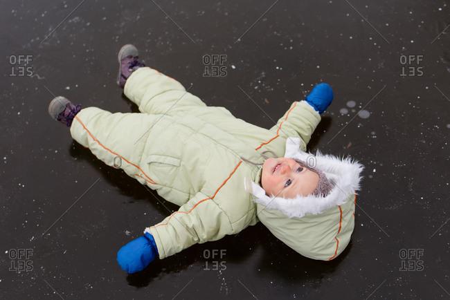 Cute baby boy lying on frozen lake looking upwards