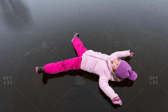 Little girl lying on the frozen lake in winter