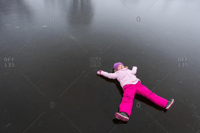 Girl child lying on frozen lake surface