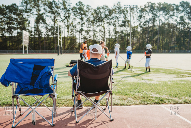Person sitting in folding chair watching football practice