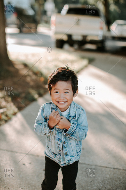 Smiling boy wearing a denim jacket standing on the sidewalk