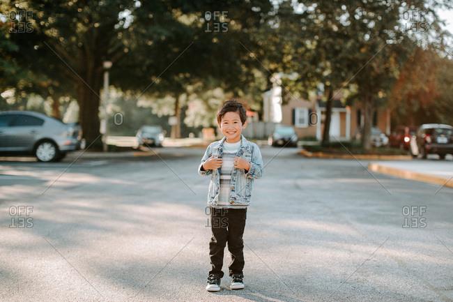 Smiling boy wearing a denim jacket standing outside