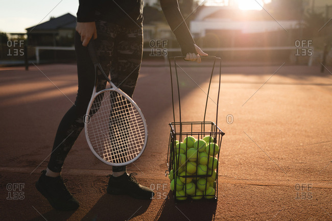 Tennis player practicing tennis in ground on a sunny day