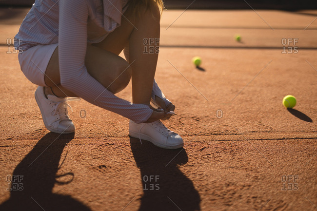 Tennis player tying shoelace in ground on a sunny day