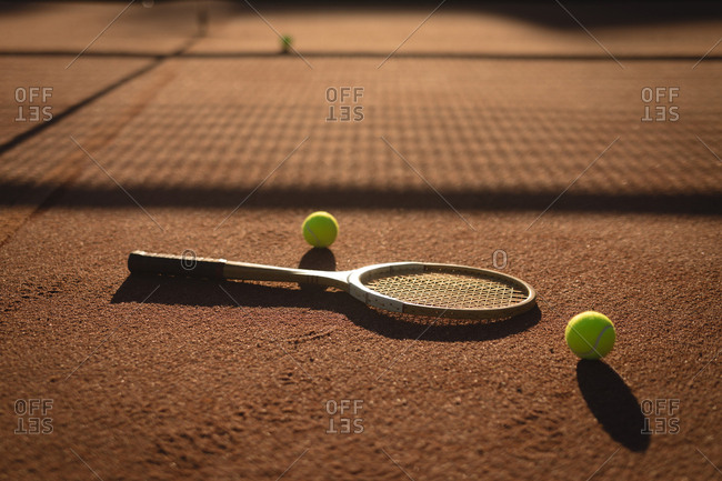 Tennis ball and racket in ground on a sunny day