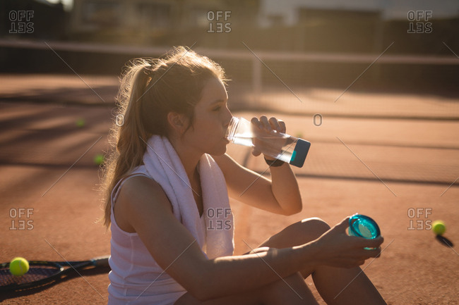 Tennis player drinking water after workout on a sunny day