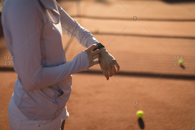 Mid section of tennis player using smart watch in ground on a sunny day