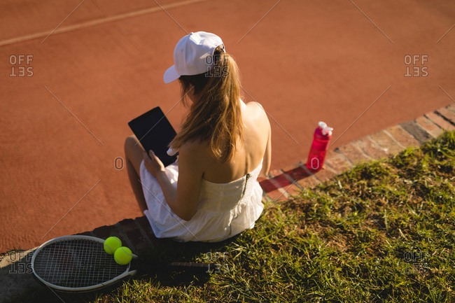 Fit woman using digital tablet while relaxing in ground on a sunny day
