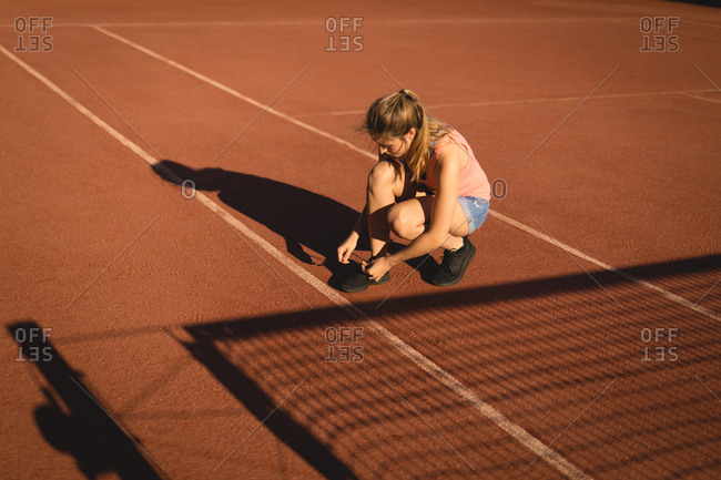 Player tying shoelace in ground on a sunny day