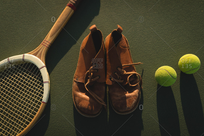 Close-up of tennis ball, sports shoes and racket in ground