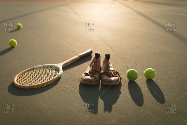 Tennis ball, sports shoes and racket in ground on a sunny day