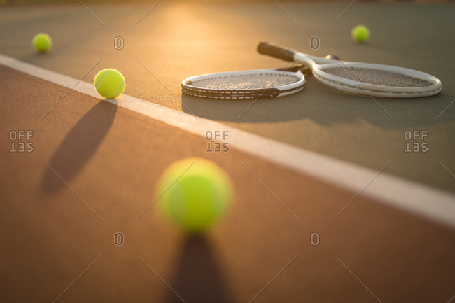 Tennis balls and rackets in ground on a sunny day