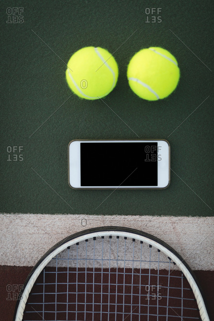Overhead of mobile phone, racket and tennis ball in ground