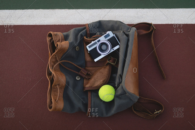Overhead of digital camera, tennis ball and bag on ground