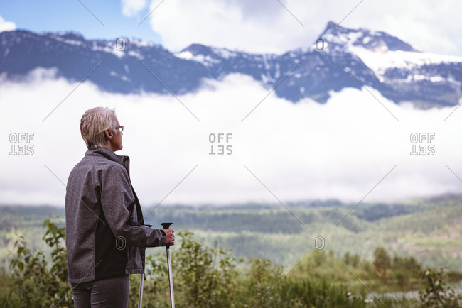 Senior woman hiker standing with hiking poles in the forest