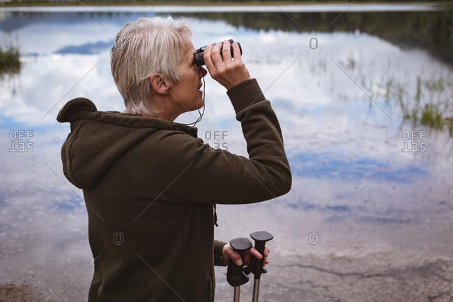 Senior woman hiker looking through binoculars in the forest