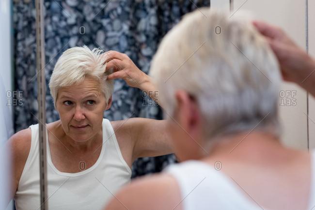 Senior woman looking in the mirror in the bathroom