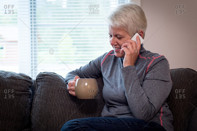 Senior woman talking on mobile phone while drinking coffee at home