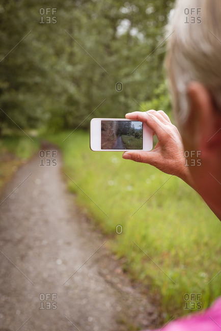 Rear view of senior woman hiker taking photograph with smartphone