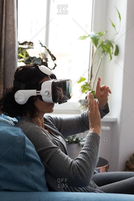 Woman using virtual reality headset at home