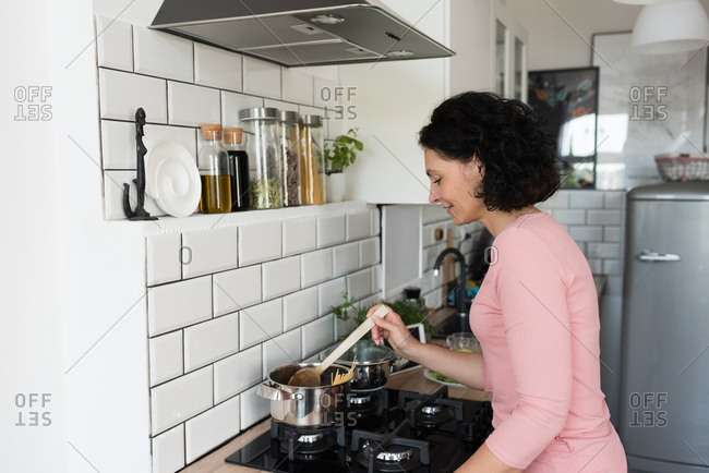 Woman standing and preparing meal in kitchen at home