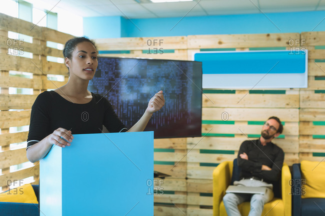 Confident female executive giving presentation in office