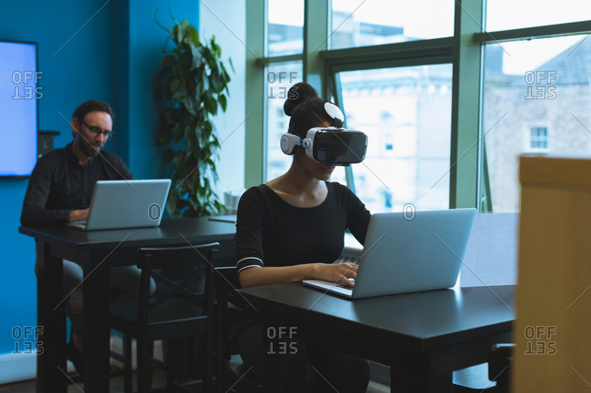 Executives using virtual reality headset while working on laptop at table