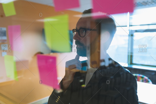 Male executive reading stick notes in office