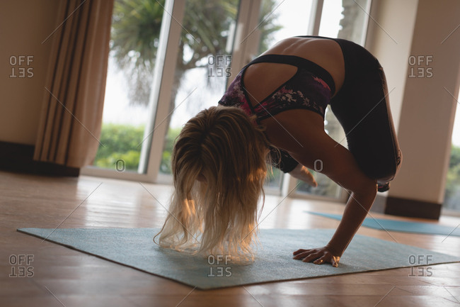 Fitness woman doing yoga handstand in yoga class