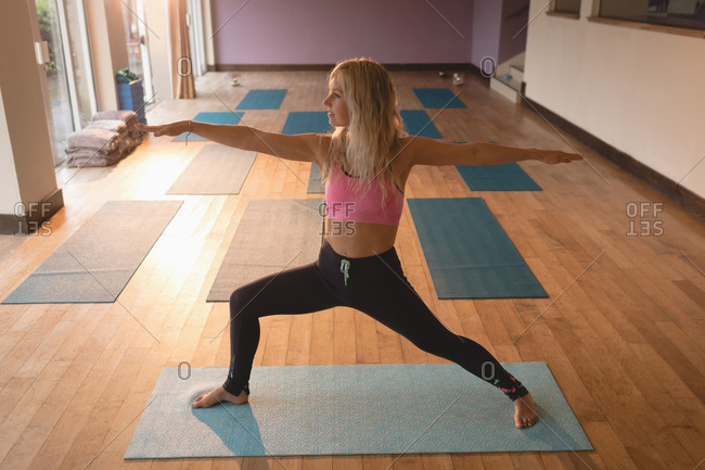 Fit woman doing yoga exercise in yoga class