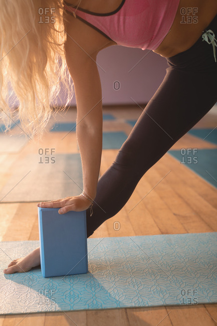 Fit woman doing stretching exercise in yoga class