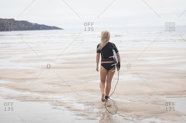 Female surfer with surfboard walking towards the sea on a sunny day