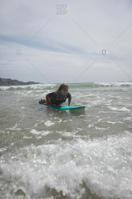 Female surfer swimming over surfboard in the sea on a sunny day