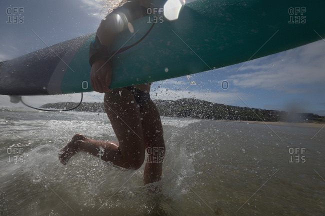 Female surfer running with surfboard in sea on a sunny da