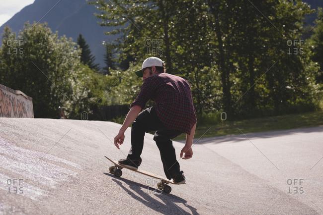 Man skating on skateboard in skate park on a sunny day