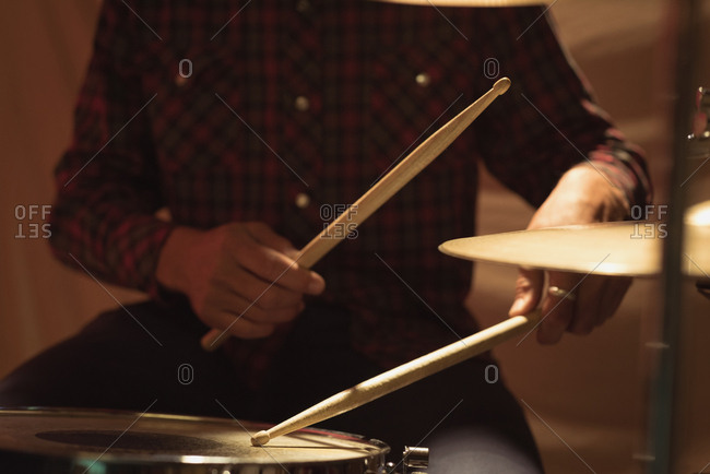 Mid section of drummer playing on drum set at studio