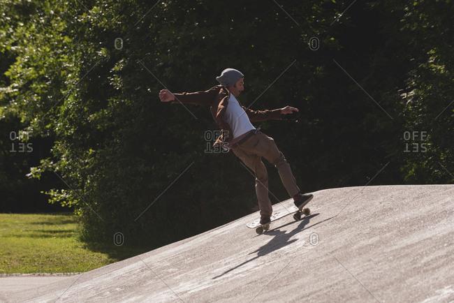 Skateboarder skating on skateboard in skate park on a sunny day