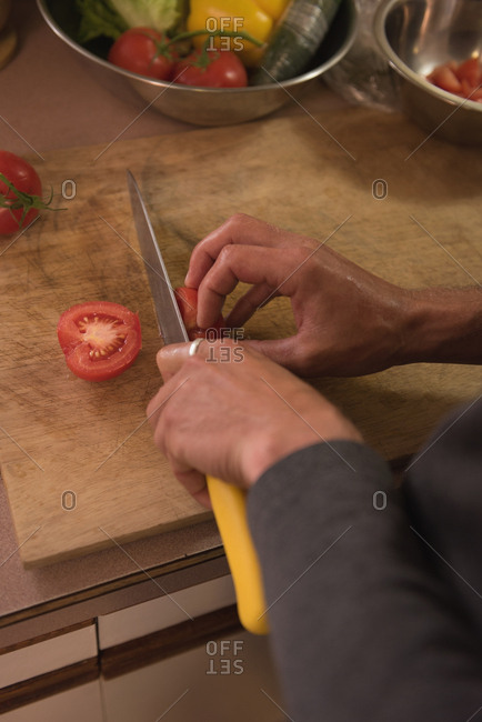 Man slicing tomato on cutting board in kitchen